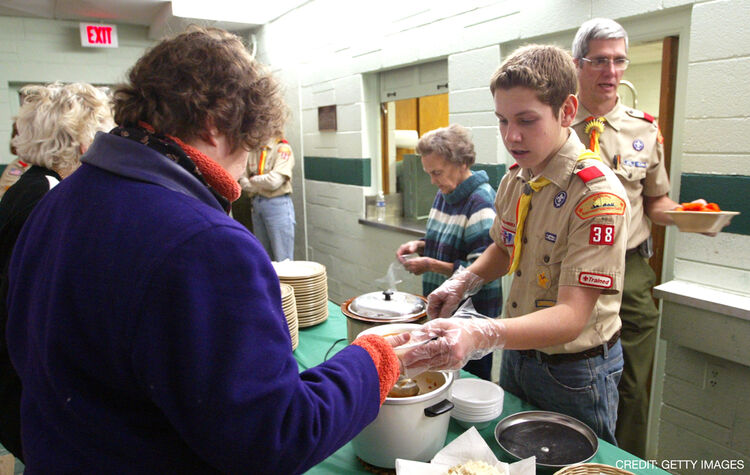 DES PLAINES, IL - JANUARY 5: Matthew Stieve of Boy Scout Troop 38 (2nd-R) serves soup to a guest at First United Methodist Church January 5, 2004 in Des Plaines, Illinois. Volunteers involved in a program called 'Bessie's Table' prepare and serve dinner to individuals or family members who are either unemployed, underemployed or just looking for a warm meal. Donations come from local grocery stores and other local companies. The program, which operates only on Monday evenings, serves an average of 70 people. (Photo by Tim Boyle/Getty Images)