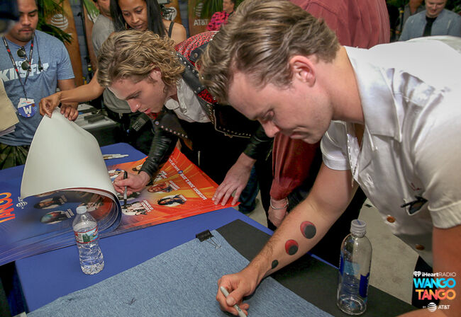 Luke Hemmings and Ashton Irwin of 5 Seconds of Summer sign posters backstage at the 2018 iHeartRadio Wango Tango by AT&T at Banc of California Stadium on June 2, 2018 in Los Angeles, California