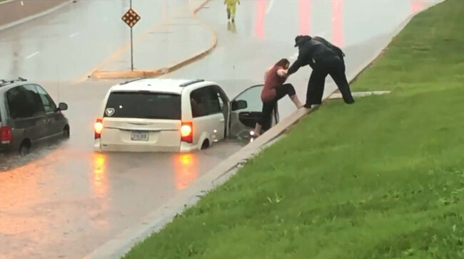 Rebecca Hovick helped out of her flooded vehicle by Ames police.  WHO TV