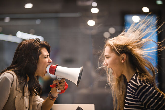 Angry female manager yelling at her colleague through megaphone. (Credit: 	iStock / Getty Images Plus)