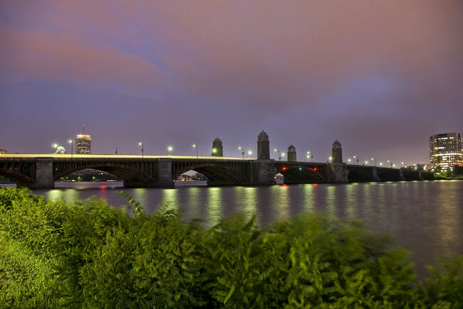 Longfellow bridge stretches across the Charles River at dusk as seen from behind shrubs on the Esplanade. (Credit: Kalim Saliba/ Getty Images /Royalty-Free)