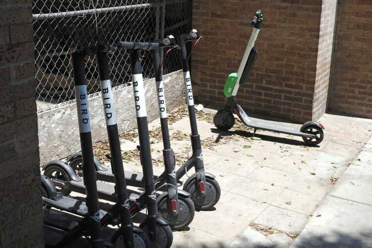 Shared electric scooters are parked on a street in Santa Monica, California, on July 13, 2018. - Cities across the U.S. are grappling with the growing trend of electric scooters which users can unlock with a smartphone app. Scooter startups including Bird and Lime allow riders to park them anywhere that doesn't block pedestrian walkways but residents in some cities, including Los Angeles, say they often litter sidewalks and can pose a danger to pedestrians. (Photo by Robyn Beck / AFP)