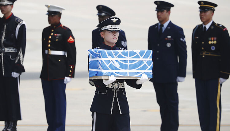 A soldier carries a casket containing the remains of a US soldier killed during the 1950-53 Korean War, after arriving from North Korea at Osan Air Base in Pyeongtaek