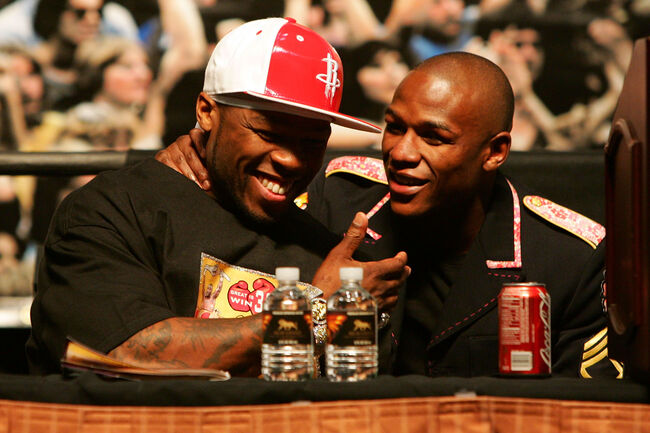 Oscar De La Hoya v Floyd Mayweather Jr. LAS VEGAS - MAY 05: (L-R) Rapper 50 Cent and Floyd Mayweather Jr. talk during the post-fight news conference after Mayweather defeated Oscar De La Hoya by split decision after their WBC super welterweight championship fight at the MGM Grand Garden Arena May 5, 2007 in Las Vegas, Nevada. (Photo by Ethan Miller/Getty Images)
