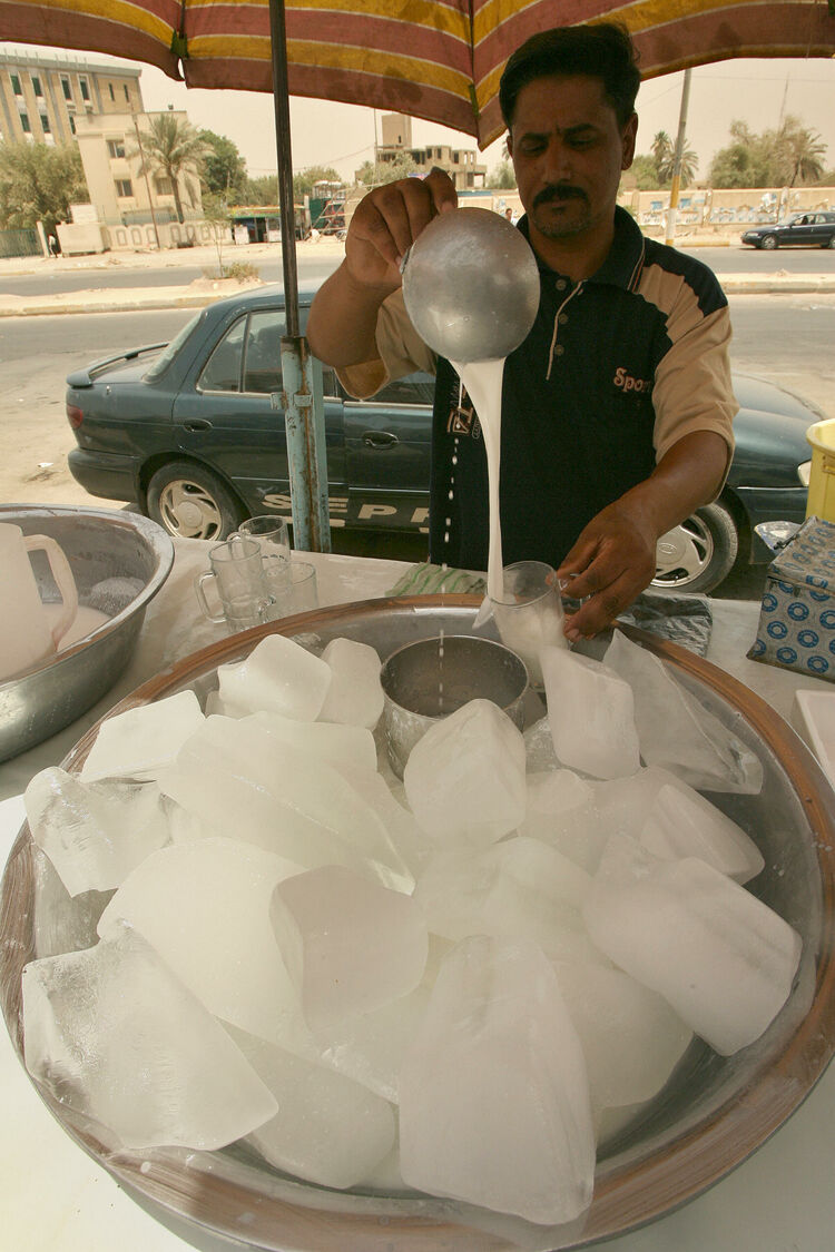 A vendor pours ice cold drinking yogurt