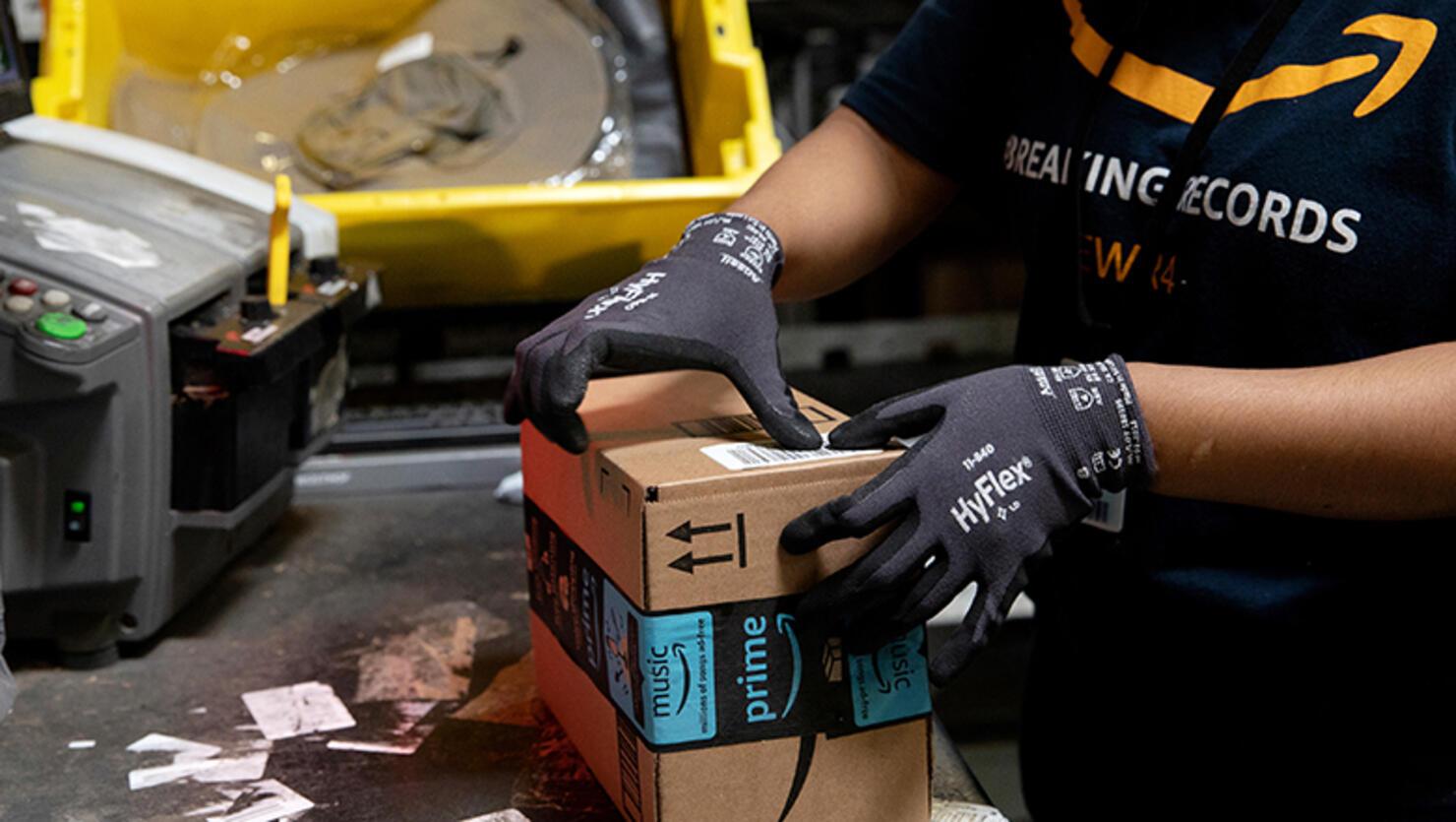 An employee packs a box at the Amazon.com Inc. fulfillment center