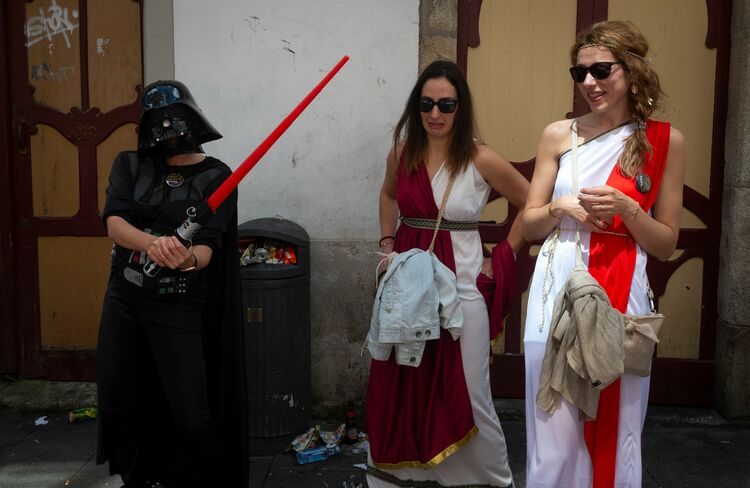 A man dressed as Darth Vader poses next to women dressed as ancient Romans during the Arde Lucus festival in Lugo, northwestern Spain, on June 16, 2018. - Arde Lucus, celebrated in the city at the end of June, is a Galician festival of touristic interest that revives the Gallaecian-Roman past of the city and commemorates its founding. (Photo by MIGUEL RIOPA / AFP) (Photo credit should read MIGUEL RIOPA/AFP/Getty Images)