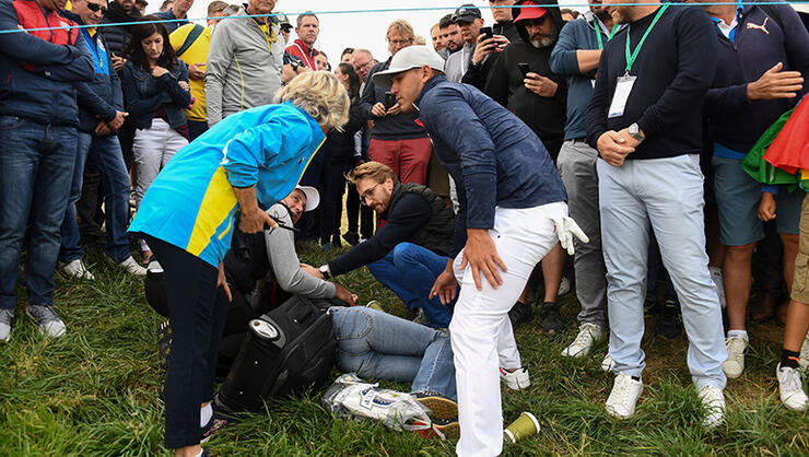 US golfer Brooks Koepka (R) reacts next to an injured spectator who fell during the fourball match on the first day of the 42nd Ryder Cup at Le Golf National Course at Saint-Quentin-en-Yvelines