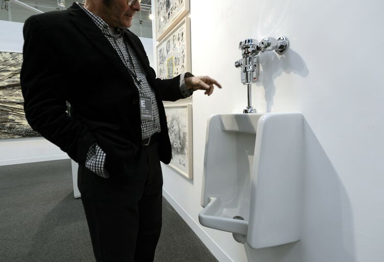 A man looks at a fully functional urinal by artist Andrew Ohanesian titled 'Urinal' during the press preview at the 2013 Armory Show, one of the world's top art events featuring the most influential artworks of the 20th and 21st centuries, at Pier 92 and 94 in New York March 6, 2013. The Armory Show Centennial Edition kicks off Armory Arts Week . AFP PHOTO / TIMOTHY A. CLARY (Photo credit should read TIMOTHY A. CLARY/AFP/Getty Images)