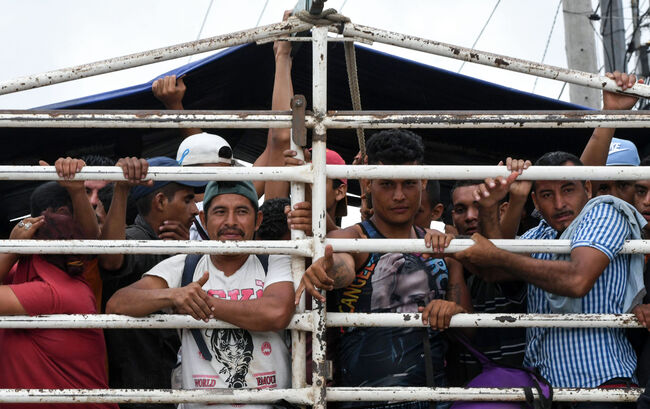 TOPSHOT - Honduran migrants aboard a truck arrive in in Guatemala City, while taking part in a caravan towards the United States, on October 17, 2018. - A migrant caravan set out on October 13 from the impoverished, violence-plagued country and was headed north on the long journey through Guatemala and Mexico to the US border. President Donald Trump warned Honduras he will cut millions of dollars in aid if the group of about 2,000 migrants is allowed to reach the United States. (Photo by ORLANDO SIERRA / AFP) (Photo credit should read ORLANDO SIERRA/AFP/Getty Images)