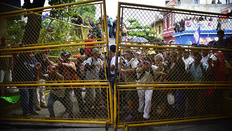 Honduran migrants heading in a caravan to the US push to tear down the gate of the Guatemala-Mexico international border bridge in Ciudad Hidalgo, Chiapas state, Mexico