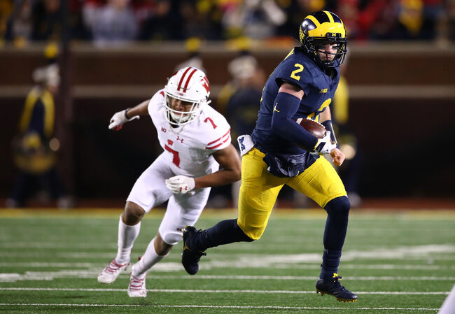 Getty Images - Michigan QB Shea Patterson makes Wisconsin's Reggie Pearson miss
