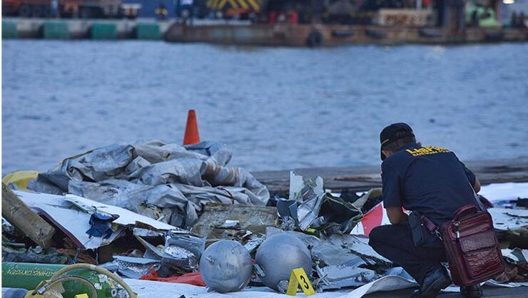 A forensic investigator looks through the remains of Lion Air flight JT 610 at the Tanjung Priok port on October 29, 2018 in Jakarta, Indonesia.