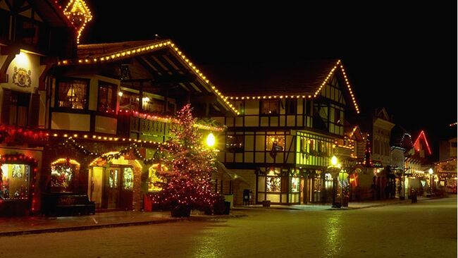 Swiss-style buildings which look like chalets, are lit up with colored lights at Christmastime in Leavenworth, Washington