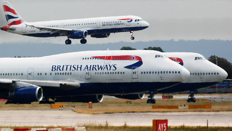A British Airways plane lands as two other grounded planes sit on the runway at Heathrow Airport, Terminal one