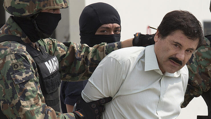 Drug trafficker Joaquin 'El Chapo' Guzman is escorted to a helicopter by Mexican security forces