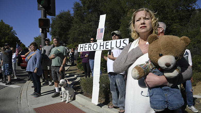 Brina Baird-Gerber holds her hand over her heart as the procession carrying the body of Ventura County Sheriff Sgt. Ron Helus, who was killed in a mass shooting at the Borderline Bar and Grill