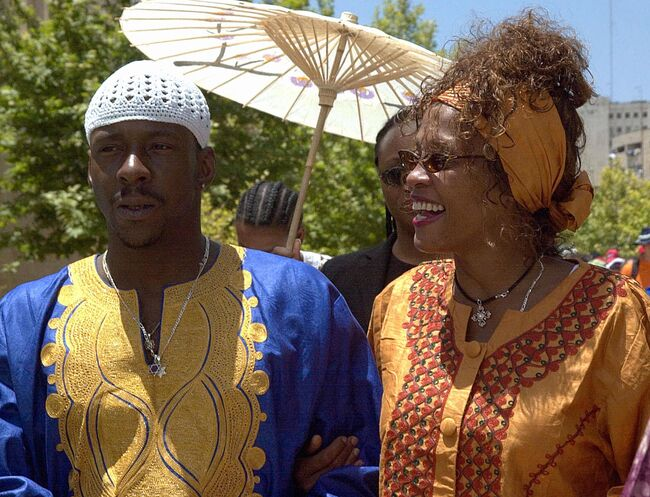 FILES-MIDEAST-ISRAEL-WHITNEY HOUSTON (FILES)US singer and actress Whitney Houston(R) smiles as she walks with her husband Bobby Brown next to the 'Wailing Wall' or Western Wall in the old city of Jerusalem 28 May 2003. The rocky marriage of Houston, whose popular tunes include 'Love is a Contact Sport,' has suffered another jolt after her husband, singer Bobby Brown. Brown was formally charged 10 December 2003 with beating her in the couple's home in a Atlanta suburb. Fulton County police spokesman Kurtis Young said the altercation inside the mansion near Alpharetta, Georgia, had forced the world-famous diva to plead for help in a frantic emergency call to police. The reason for the argument was not mentioned, but the marriage of 13 years has had a number of rough patches before. AFP PHOTO/STR / AFP PHOTO (Photo credit should read /AFP/Getty Images)