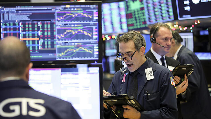 Traders work at the New York Stock Exchange in New York
