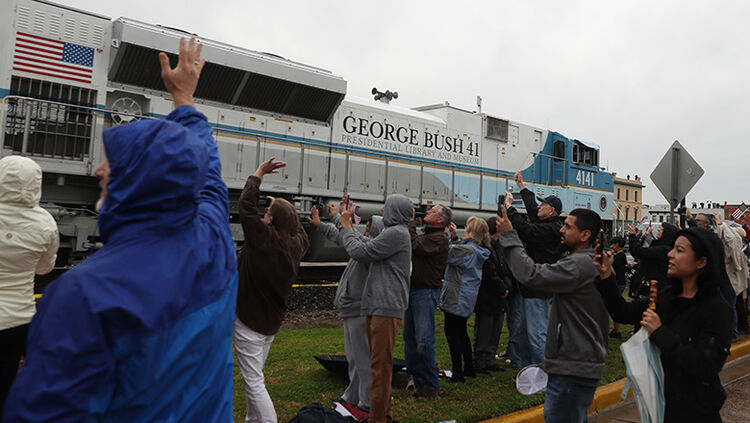 People wave at the train carrying the casket of former U.S. President George H.W. Bush to the George H.W. Bush Presidential Library at Texas A&M University