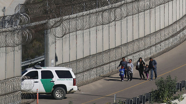 Migrants walk while being taken into custody by the U.S. Border Patrol after crossing the U.S.-Mexico border fence and turning themselves in