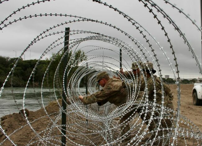 Soldiers install barbed wire on border