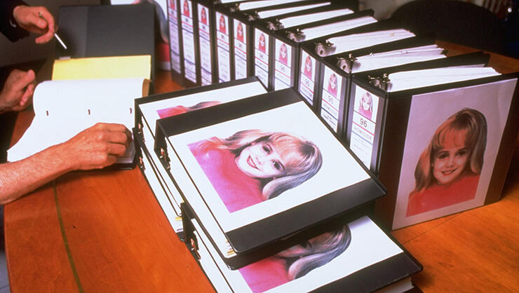 Murdered 6-yr-old beauty queen JonBenet Ramsey's image amblazoned on dozens of binders crammed w. investigators's reports for case which still unsolved
