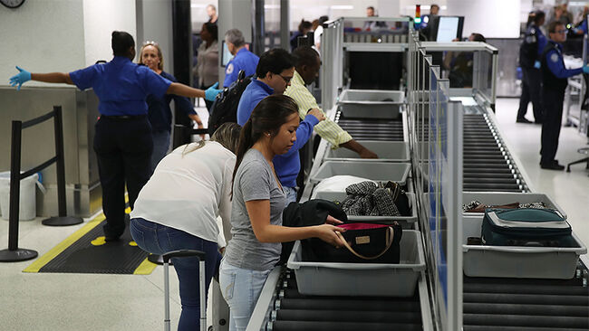 Travelers use the automated screening lanes funded by American Airlines and installed by the Transportation Security Administration at Miami International Airport