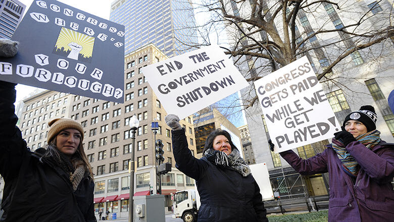 EPA employee Rosanne Sawaya-Obrien (C) holds her sign calling for an end to the government shutdown during a rally and protest by government workers and concerned citizens at Post Office Square near the Federal building, headquarters for the EPA and IRS in Boston