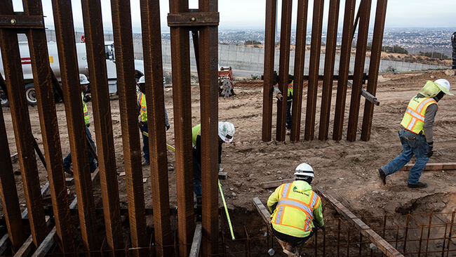 A construction crew works on replacing the US-Mexico border fence as seen from Tijuana, in Baja California state, Mexico