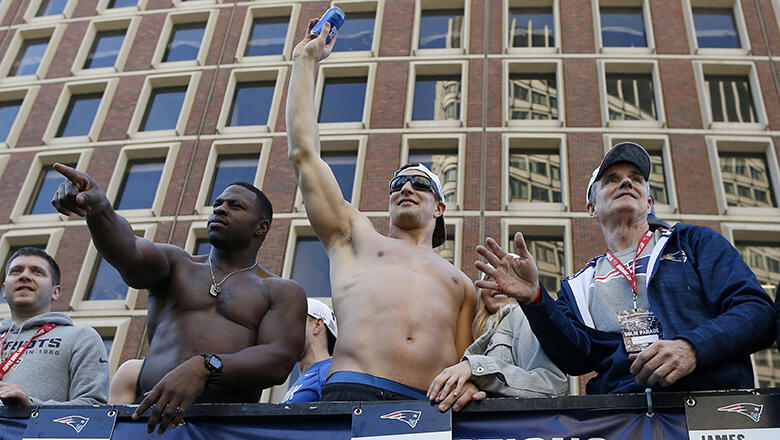 Rob Gronkowski, center, catches a beer that was thrown to him from the crowd during the New England Patriots Super Bowl LIII victory parade in Boston