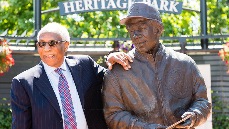 Former Cleveland Indians manager and player Frank Robinson stands with a new statue commemorating his career