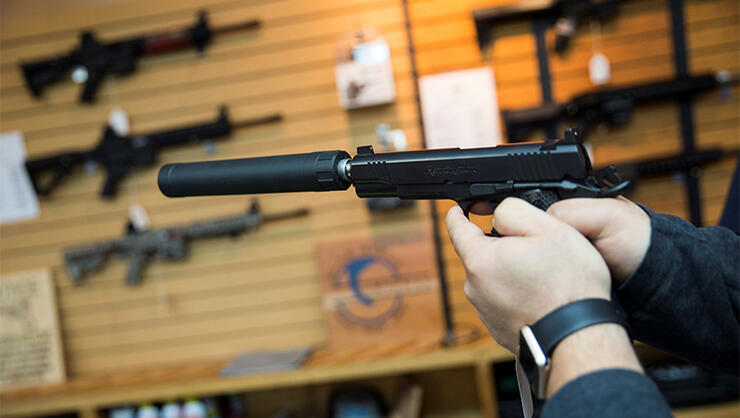 A customer tries out a Remington 1911 equipped with a silencer