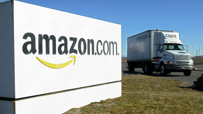 A truck drives by an Amazon fulfillment center