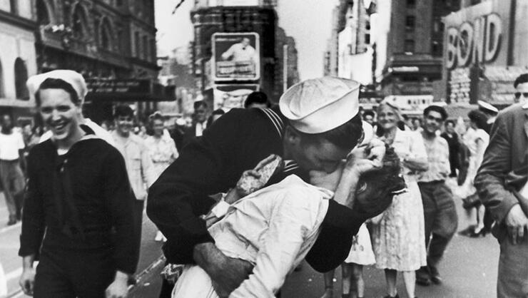 A jubilant American sailor clutching a white-uniformed nurse in a back-bending, passionate kiss as he vents his joy while thousands jam Times Square to celebrate the long awaited-victory over Japan