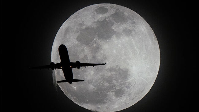 A plane flies past the super moon in Los Angeles,