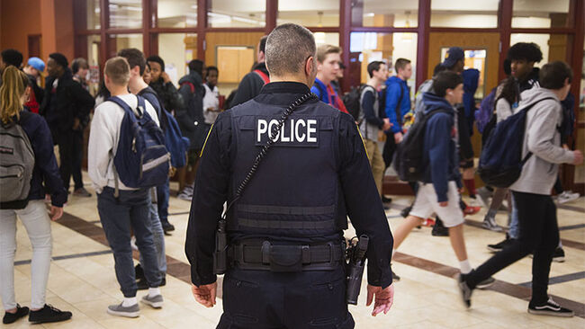 A school resource officer stands outside the main office as students exit for the weekend
