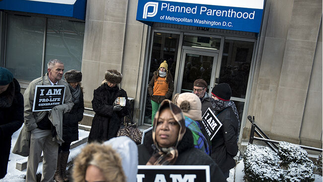 A pro-choice escort waits at the doors of a Planned Parenthood as pro-life activists rally during a protest