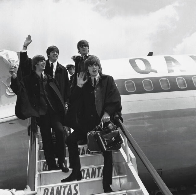 The Beatles (L to R) Ringo Starr, Paul McCartney, John Lennon and George Harrison wave to fans July 2, 1964 as they return to London from a tour of Australia. Photo by Getty Images