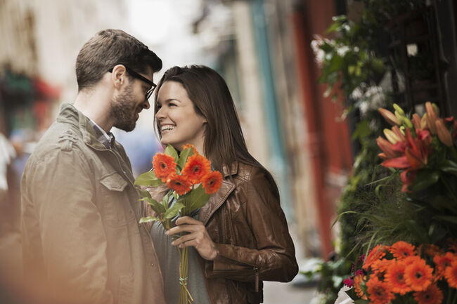 A man and woman by a flower stall in the city, holding a bunch of bright red flowers.
