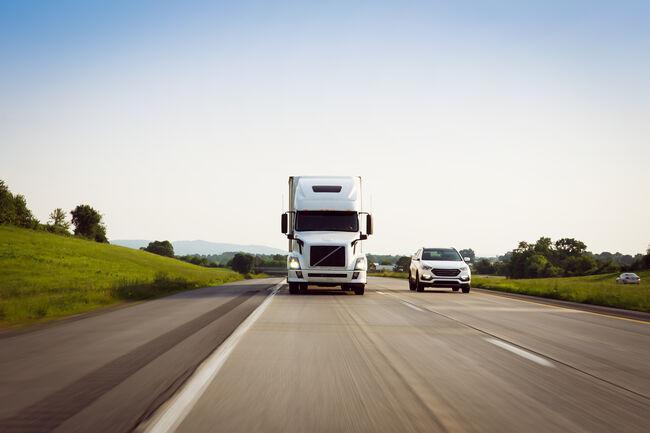 White 18 wheeler semi-truck driving on highway