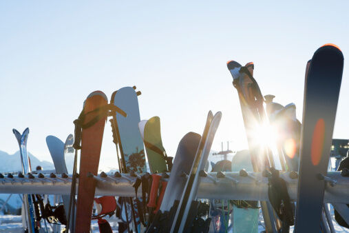 Sun shining through outdoor rack of skis
