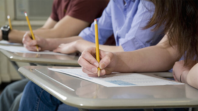 Students sitting at desks and writing