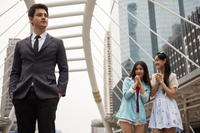 Asian girls look at handsome businessman
