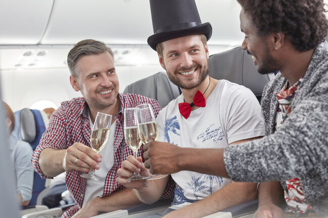 Young male friends toasting champagne glasses on airplane