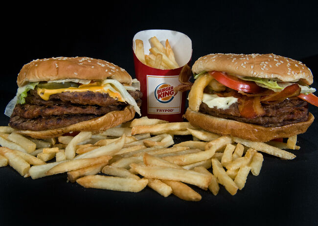 Burger King's two big boy burgers, the 'BK Quad Stacker' (L) with four beef patties, topped with bacon, cheese, sauce, lettuce, pickles, onions seen August 19, 2009, in Washington, DC. The 'BK Quad Stacker' weighs in with 1010 calories, 70 grams of fat, 30 mg of saturated fat, 3 grams trans fat, 210 mg cholesterol, 34 carbs, 6 grams sugar, 64 grams protein, and 1800 mg sodium. Burger King's 'Angry Triple Whopper' (R) with three beef patties, bacon, pepper jack cheese, Jalapeno peppers, 'Angry' onions, tomatoes, lettuce and 'Angry' sauce ngry Whopper' boasts 1360 calories, 91 grams of fat, 33 grams trans fat, 235 mg cholesterol, 59 grams of carbs, 13 grams sugar, 77 grams protein, and 1830 mg sodium, plus the 500 calorie French Fries. (Photo credit PAUL J. RICHARDS/AFP/Getty Images)