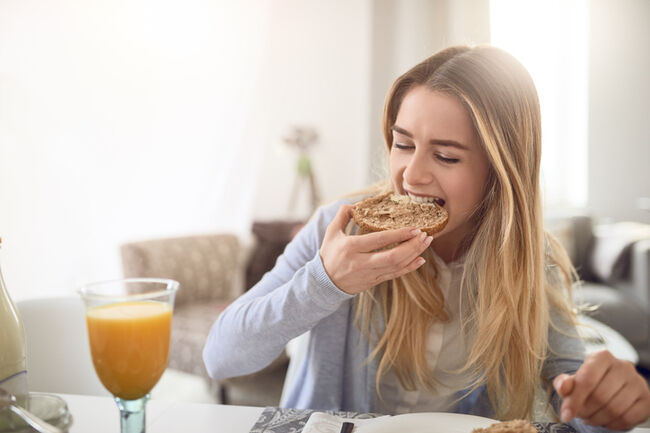 Close-Up Of Young Woman Eating Breakfast At Home