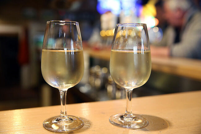 Two glasses of white wine in a bar.