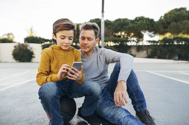 Father and son sitting on basketball outdoor court using cell phone