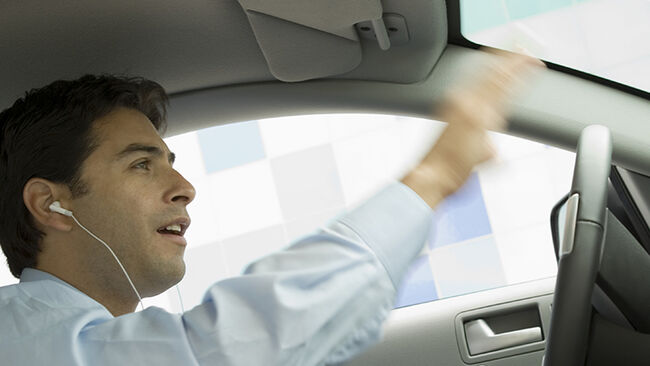 Businessman Listening to His MP3 Player While Driving